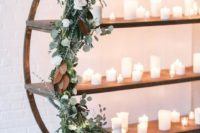 10 a winter wedding arch done with eucalyptus, white roses and magnolia plus lots of candles looks pretty modern