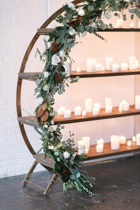 a winter wedding arch done with eucalyptus, white roses and magnolia plus lots of candles looks pretty modern