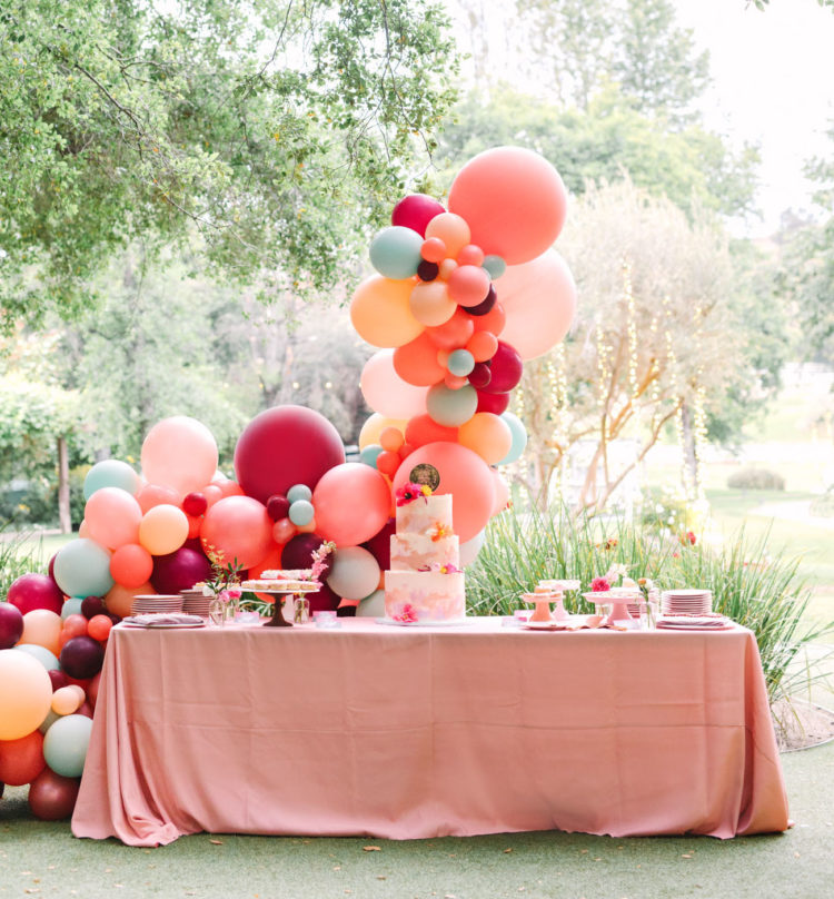 The dessert table was accented with a gorgeous colorful balloon arch behind it