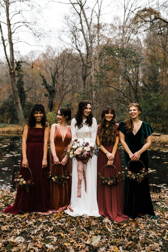 mismatching jewel tone velvet and satin bridesmaid dresses will fit both a fall and a winter wedding, too