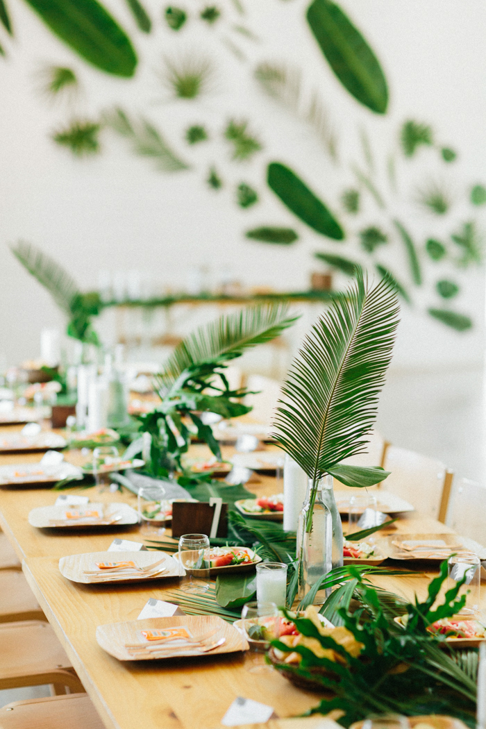 These tables with frond runners and centerpieces, tropical fruits and wooden chargers felt very tropical