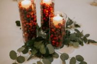 12 a simple and cozy winter wedding centerpiece of eucalyptus, candles and cranberries in tall glasses