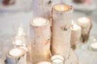 13 a simple and cozy winter wedding centerpiece of candles in glass and branch candleholders on a wood slice