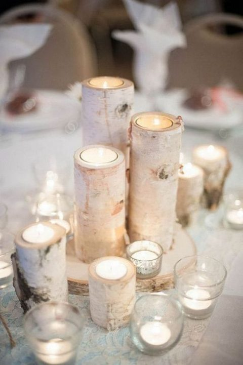 a simple and cozy winter wedding centerpiece of candles in glass and branch candleholders on a wood slice