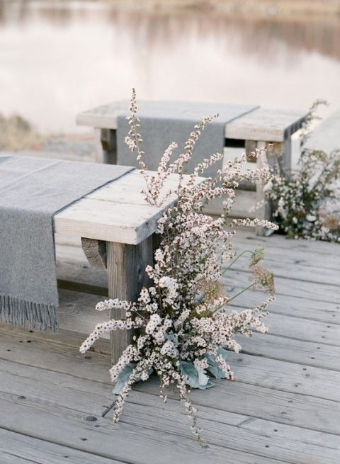 a neutral winter wedding aisle with blush blooms and dried herbs is a stylish and chic idea with a frozen feel