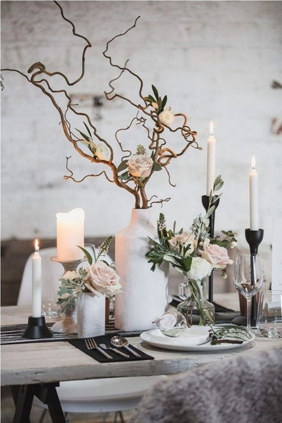 a modern winter wedding table with white vases, black candleholders, branches, blush blooms and pale greenery plus candles