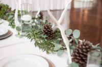 18 a greenery runner with pinecones, white candles and some antlers is a cool idea for a modern natural wedding