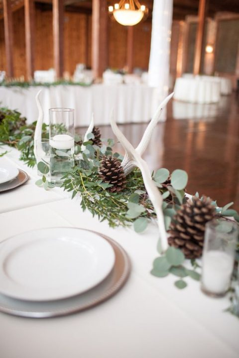 a greenery runner with pinecones, white candles and some antlers is a cool idea for a modern natural wedding