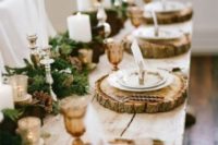 19 a gorgeous winter wedding table with wood slices, an evergreen runner with pinecones and candles of various sizes