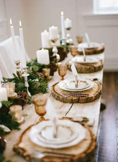 a gorgeous winter wedding table with wood slices, an evergreen runner with pinecones and candles of various sizes