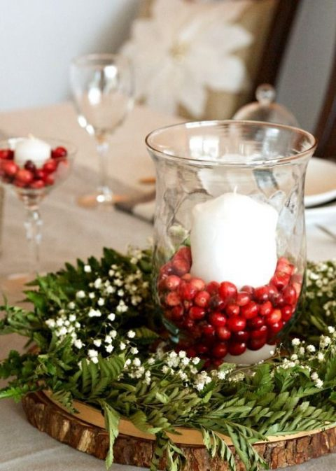 a chic rustic winter wedding centerpiece of a wood slice, greenery, baby's breath and a glass with cranberries and a candle