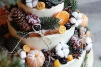 23 a gorgeous winter wedding cake with pinecones, cotton, sugared berries, citrus slices and cinnamon sticks