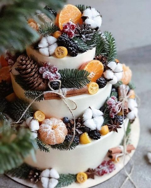 a gorgeous winter wedding cake with pinecones, cotton, sugared berries, citrus slices and cinnamon sticks