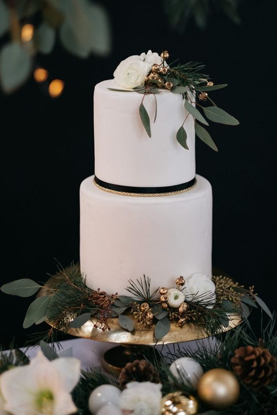 a modern white winter wedding cake with white blooms, gilded berries, evergreens and greenery