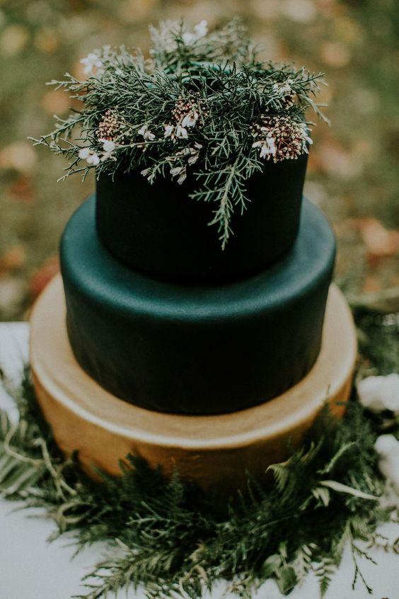 a moody winter wedding cake in black and gold topped with some greenery, blooms and berries