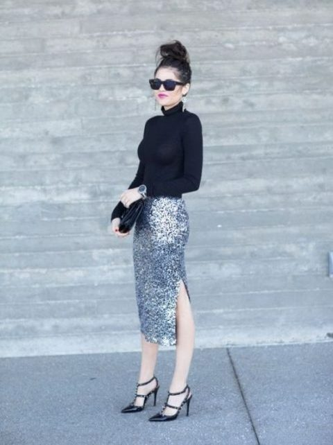 a black turtleneck, a silver pencil midi skirt with a side slit, spiked heels and statement earrings