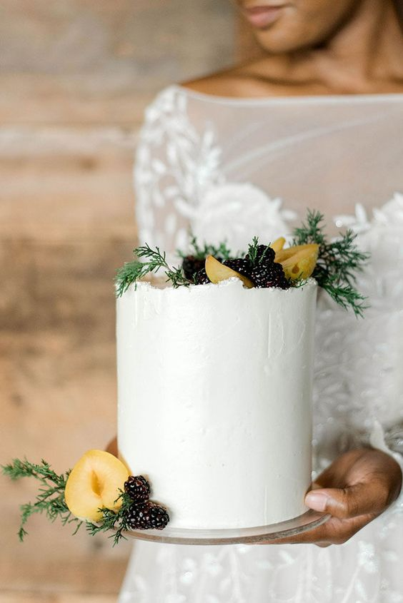a white wedding cake with a raw edge, fresh fruits and blackberries plus some greenery touches for a modern winter celebration