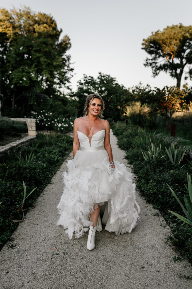 The bride was wearing a fantastic custom-made wedding dress with a plunging neckline, a feather skirt and booties