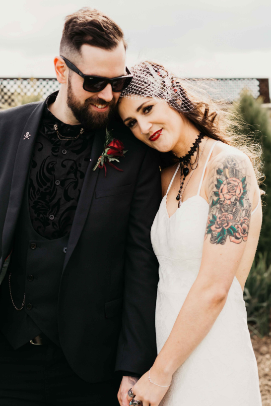 The bride was wearing a lace spaghetti strap wedding dress with a black necklace and the groom was wearing all-black with a patterned shirt
