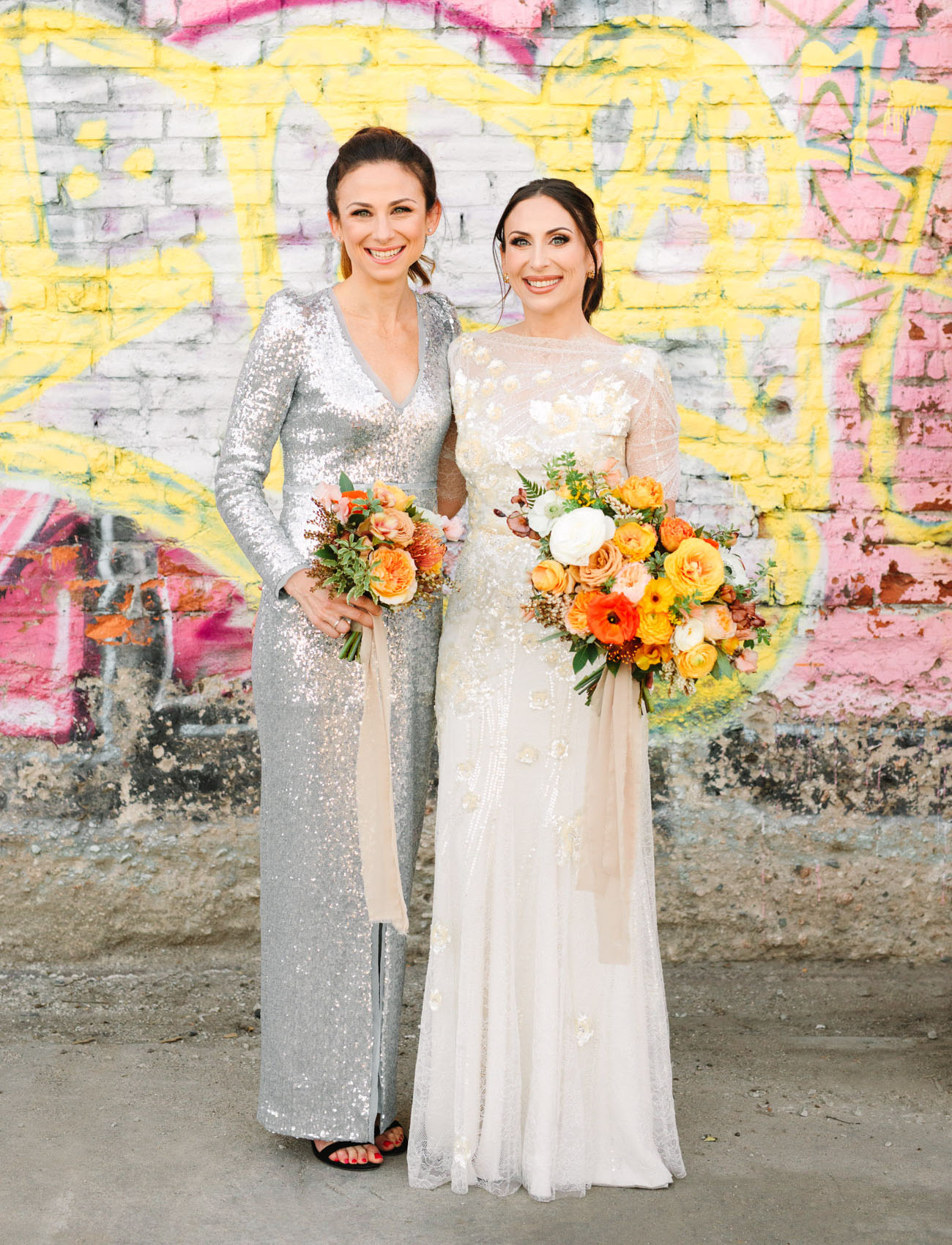 The bride was wearing a white wedding dress with embellishments and gold lace appliques, the bridesmaid was wearing a silver sequin maxi dress