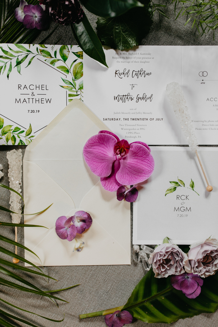 The wedding invitation suite was neutral, with black calligraphy and botanical prints