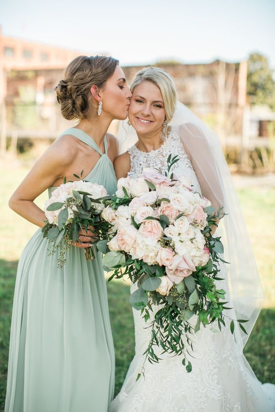 an aqua-colored maxi halter neckline bridesmaid dress and statement earrings for a bridesmaid look
