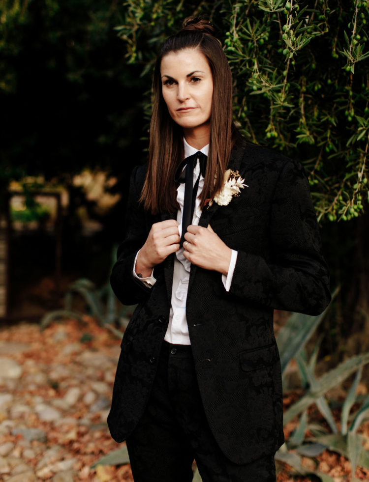 One bride was wearing a black floral suit with a bow and a white dried flower boutonniere