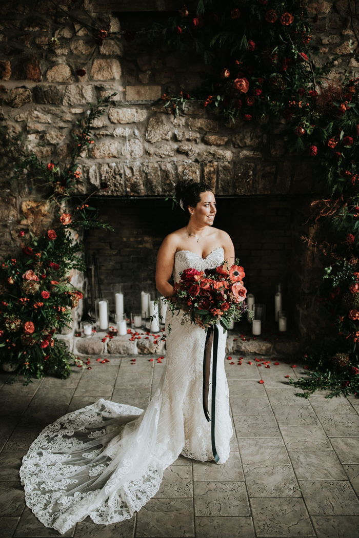 The bride was wearing a chic strapless lace sheath wedding dress with a train and carrying a red and pink wedding bouquet