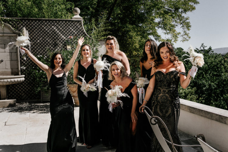 The bridesmaids were wearing elegant mismatching black maxi dresses