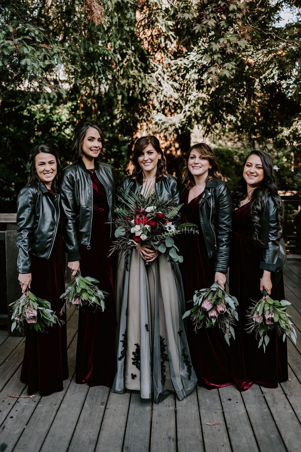 The bridesmaids were wearing mismatching burgundy velvet dresses and everyone covered up with a black leather jacket