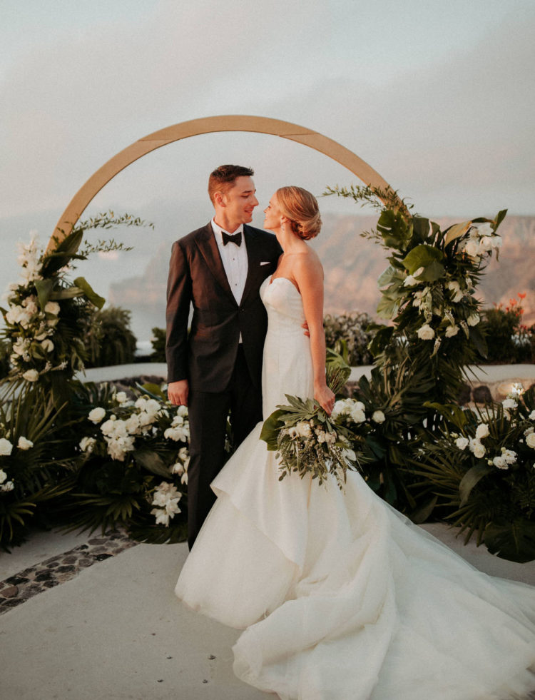 The wedding arch was a round one with lush tropical greenery and white blooms and a gorgeous view