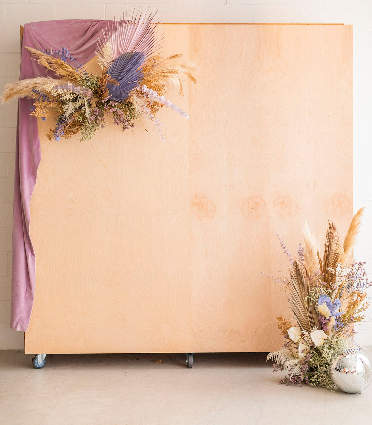 The wedding backdrop was done of plywood, with colored fronds, dried blooms and greenery