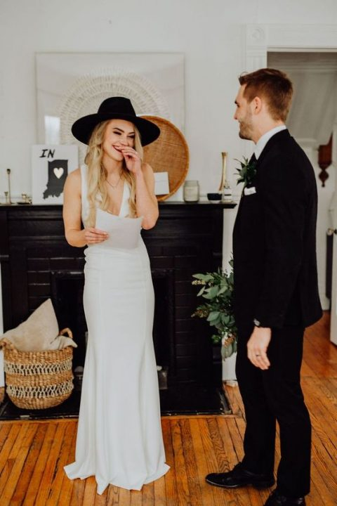 a plain fitting wedding dress with thick straps and a deep plunging neckline plus a black hat for a boho touch