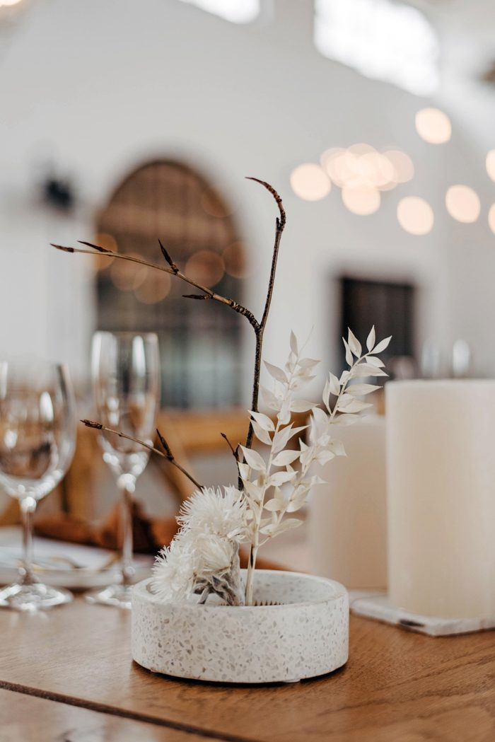 a simple and chic wedding centerpiece of branches and dried blooms in a terrazzo plate is a cool idea