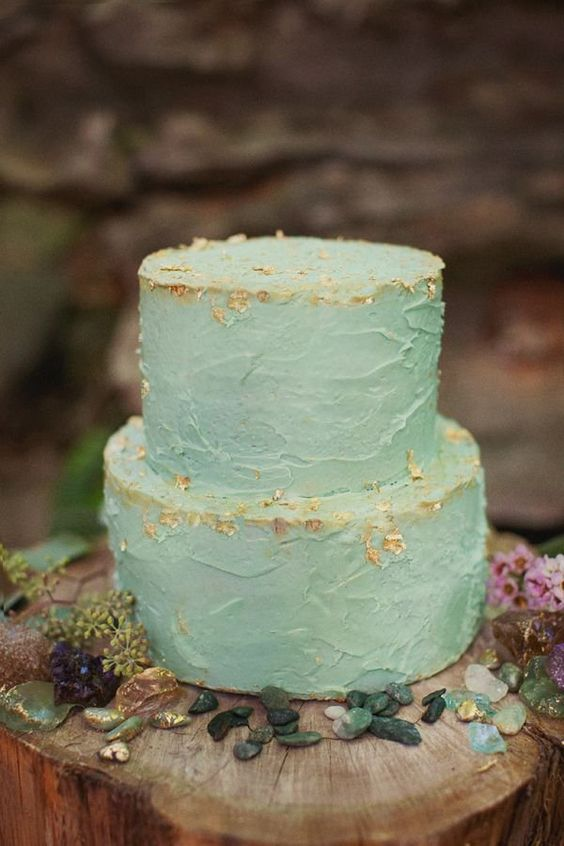 a textural aqua-colored wedding cake decorated with gold leaf looks very cool and bright