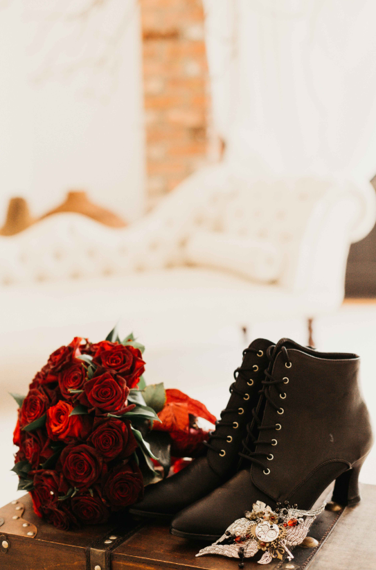 The bride was rocking black booties and carrying a red rose wedding bouquet