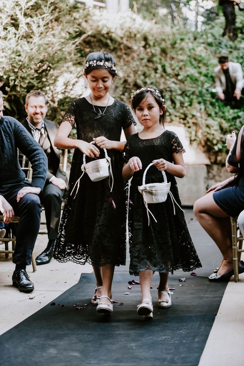 The flower girls were wearing black lace dresses