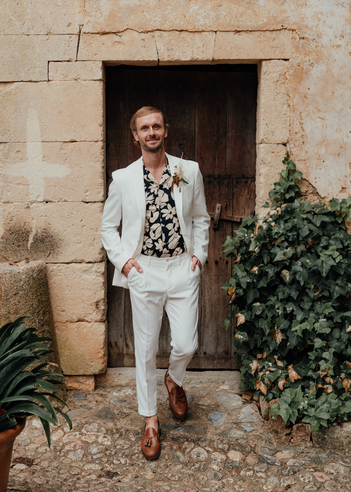 The groom was wearing a white suit, a dark floral shirt and brown moccasins for a relaxed boho look