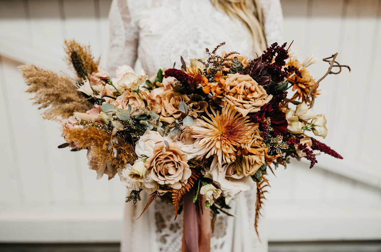 The wedding bouquet was done in rust, burgundy and peachy with pampas grass and dried herbs