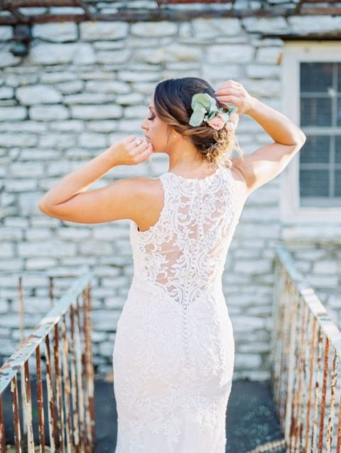 a lace fitting wedding dress with no sleeves and a cool illusion back on buttons for a twist is a chic idea