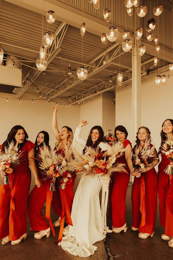 deep red jumpsuits with cap sleeves and wideleg pants and white platform shoes for boho bridesmaids