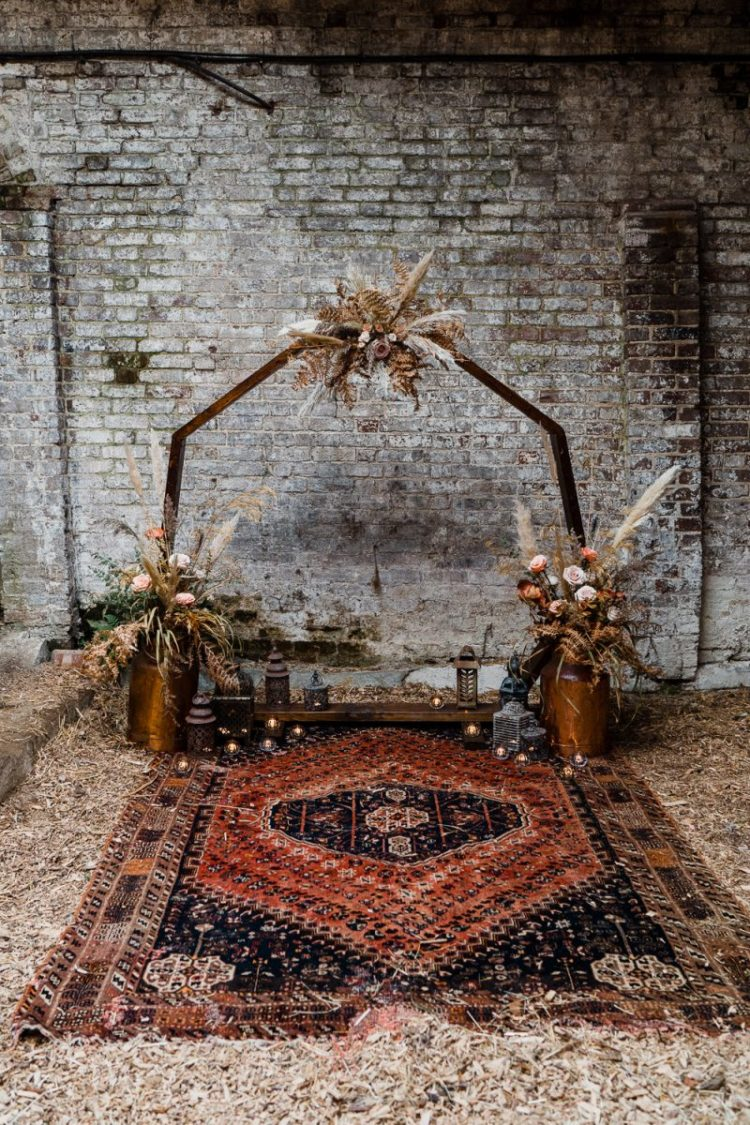 The wedding ceremony space was done with a geometric arch, lots of dried greenery and blooms and a boho rug