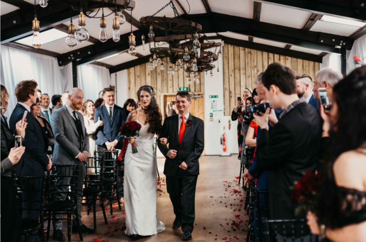 The ceremony space was done with red petals and industrial bulb chandeliers