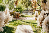 06 The wedding ceremony space was done with boho rugs, lots of pampas grass and a round arch with lush blooms and pampas grass