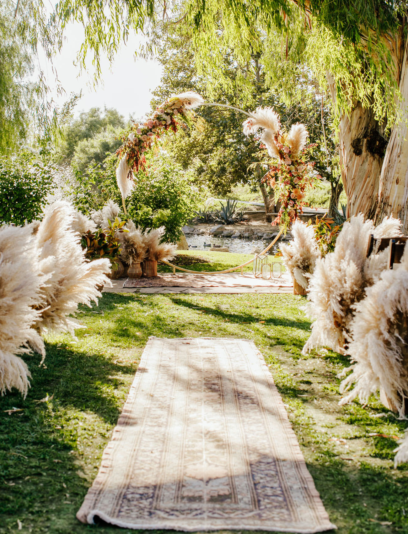 The wedding ceremony space was done with boho rugs, lots of pampas grass and a round arch with lush blooms and pampas grass