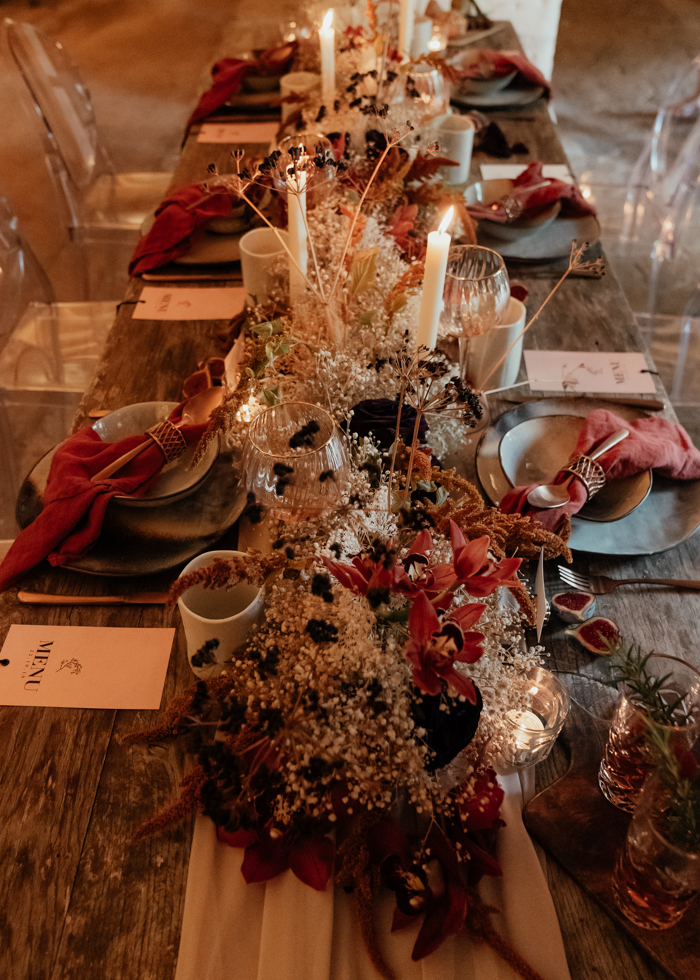 The wedding table was uncovered but with a blush runner, decorated with dried blooms and herbs, styled with dark porcelain and colorful napkins