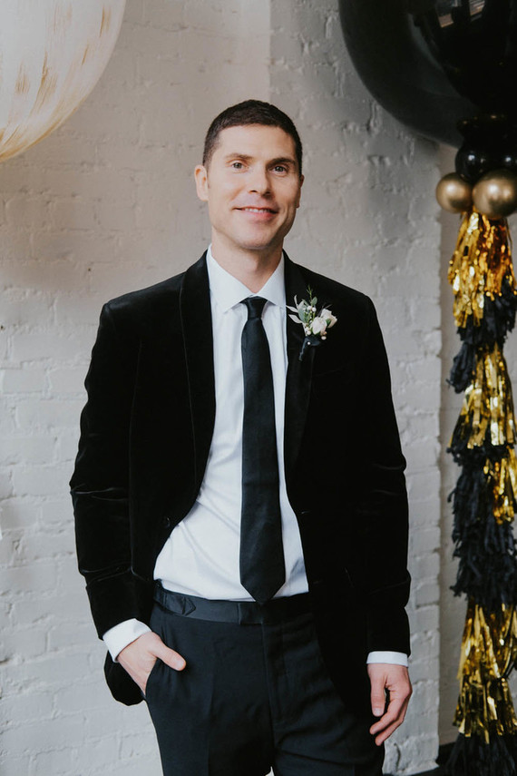 The groom was wearing a black tie and a black velvet blazer for a chic and refined look
