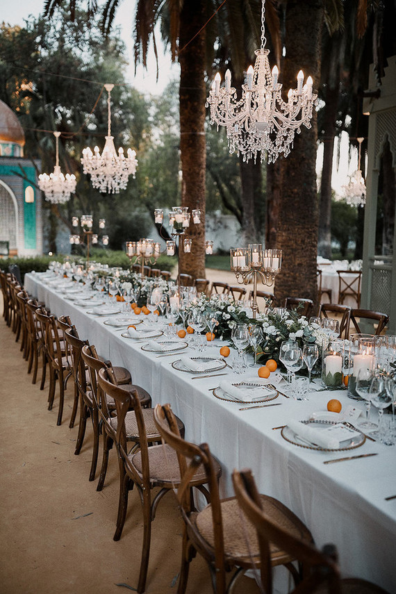 The outdoor reception was super exquisite, with greenery and white bloom runners and fruits, with candles and gorgeous chandeliers overhead