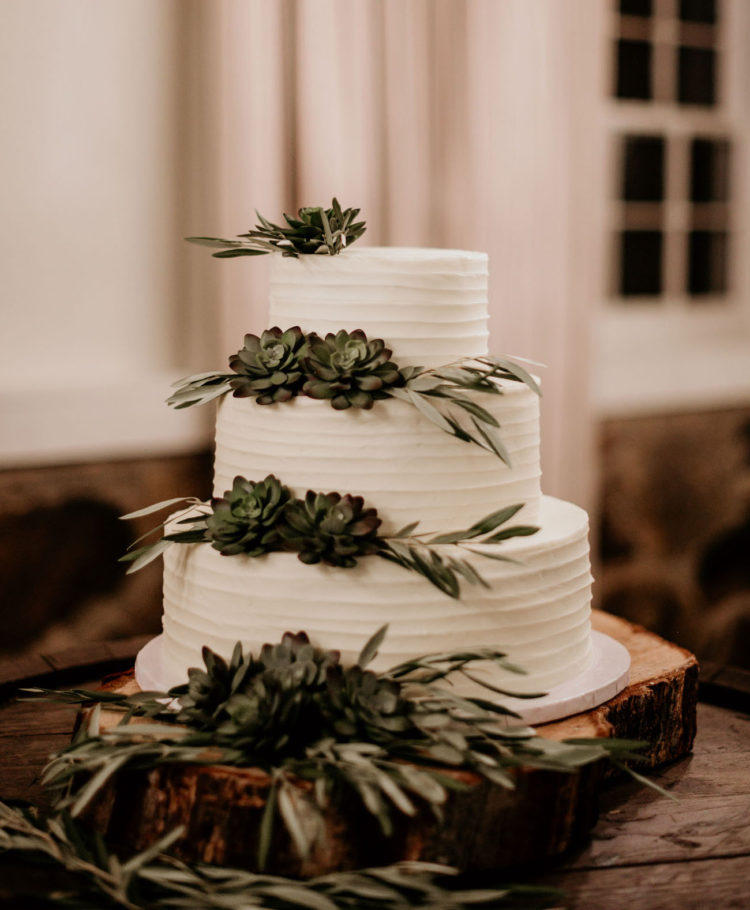 The wedding cake was simple and rustic, with greenery and succulents