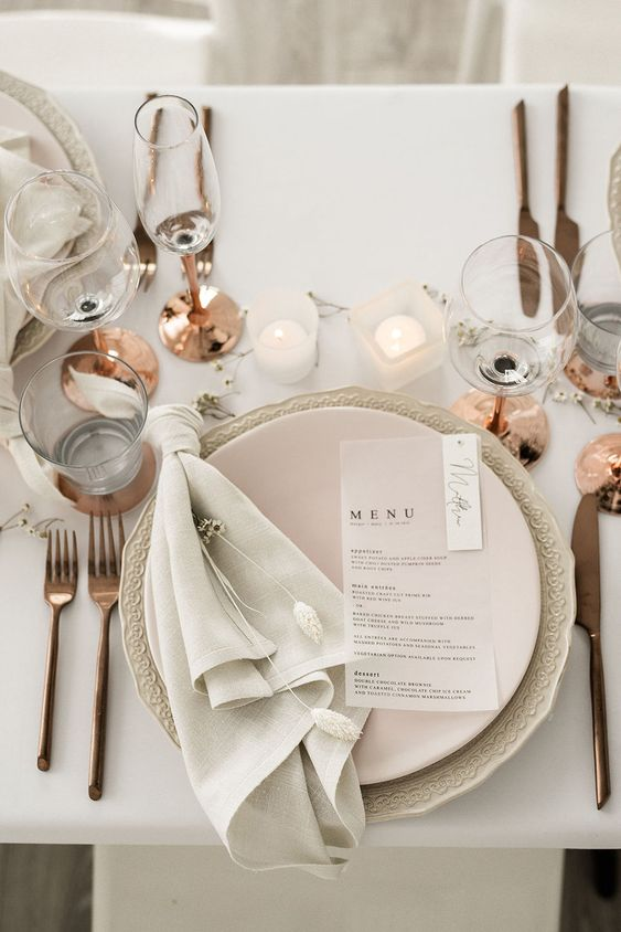 a neutral and textural wedding tablescape with cool matte plates, copper touches, candles and glasses